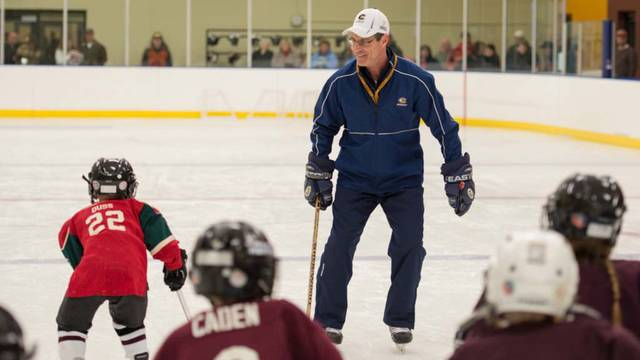 A professor working with youth hockey players.