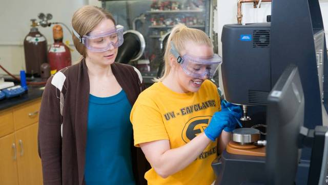 Dr. Elizabeth Glogowski watches as student Liz Stubbs focuses on her work in the materials science lab at UW-Eau Claire.