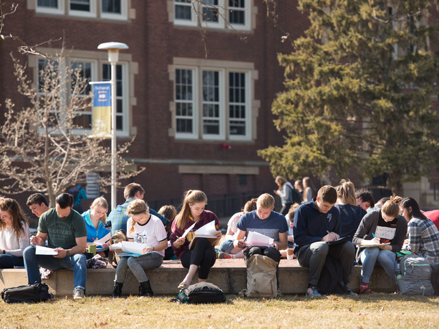 UW-Eau Claire students study in front of Schofield Hall.
