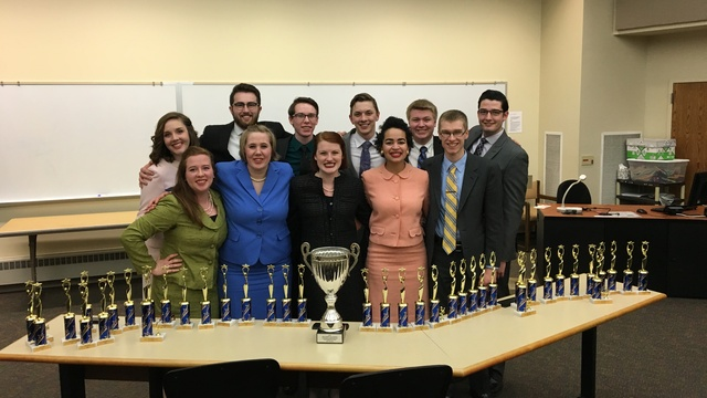 Forensics students with multiple trophies