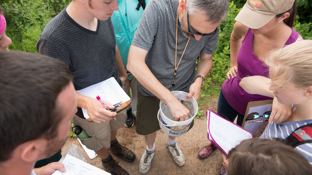 Professor showing students plant life