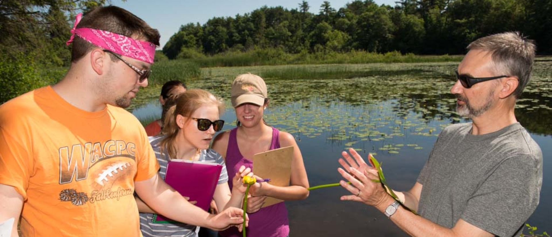Biology students and professor discussing samples out in the field