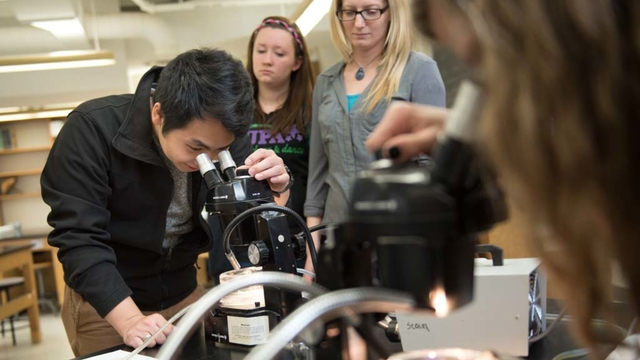 Biology students looking at microbes under a microscope in the lab.