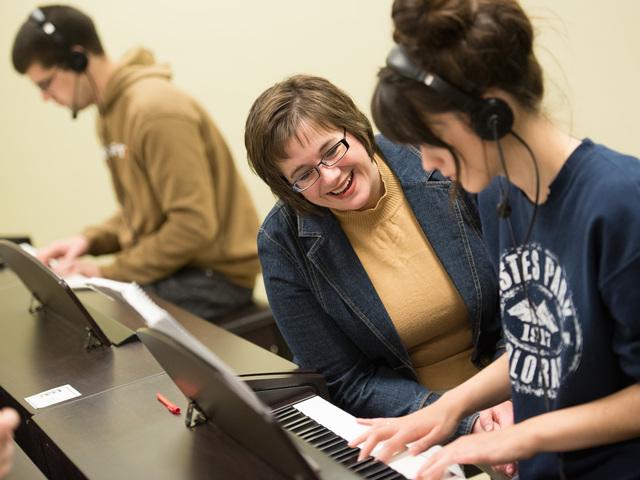 Professor Cruciani works with student on piano skills