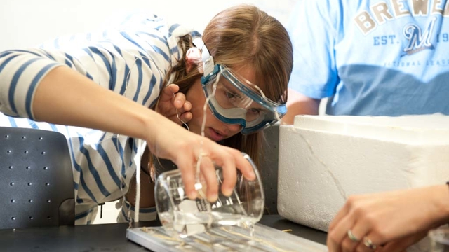 Student pours chemicals from graduated cylinder