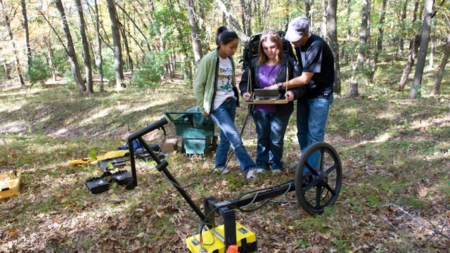 Students and a professor use geography equipment.