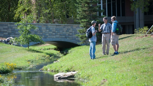 Students and a professor chat by a creek.