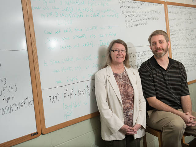 Professors sitting in front of a white board.