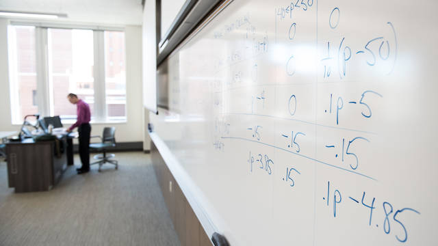 A professor and a math board.