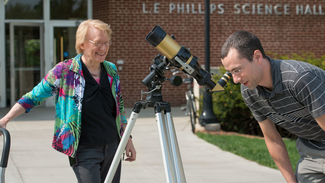 Professor and student looking through telescope