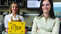 Two women proudly standing in front of cafe counter with a bright yellow open sign.