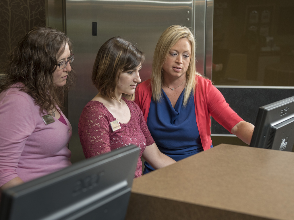 Three women looking at a computer screen infront of a bank vault.
