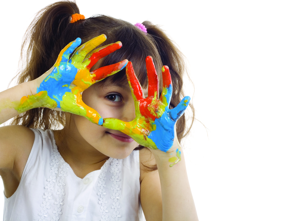 A young girl with pigtails looks through her fingers that are covered in red, yellow, blue and green paint.