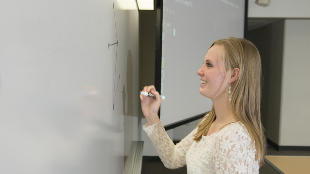 Professor writes on a white board