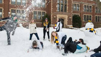 Students having snow fight in front of Schofield Hall