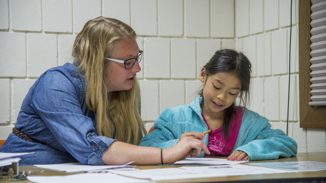 Graduate student working with a child