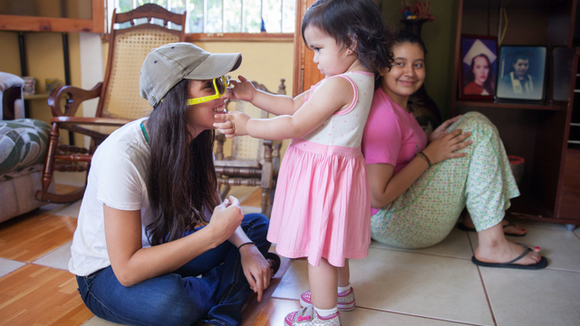 Student and little girl playing with sunglasses