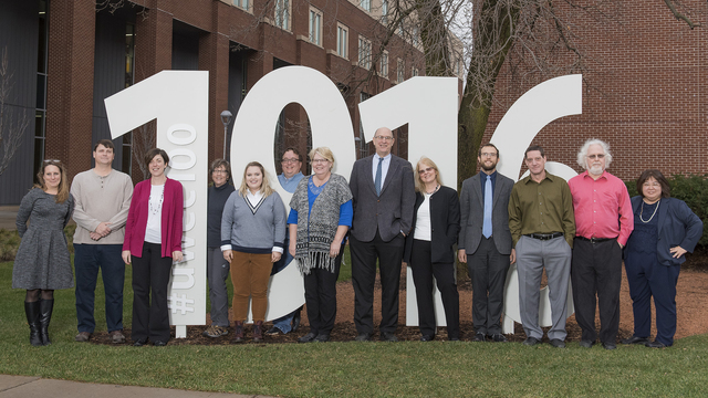 History faculty stand next to 1916 centennial sign