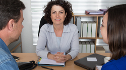 Middle aged woman faces the camera as she looks over her desk at a man and a woman.