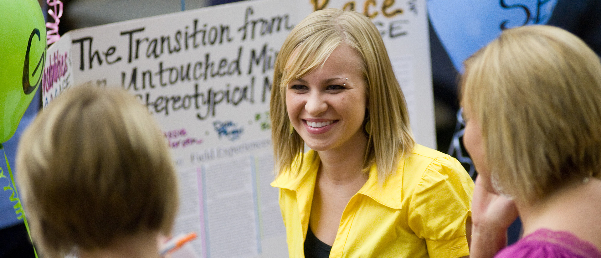 Girl in yellow top smiling at social work fair.
