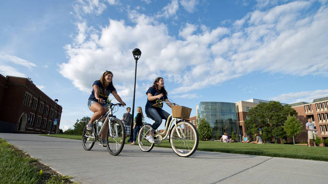 Students riding their bikes on campus.