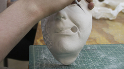 Student in studio arts class working on ceramic piece.