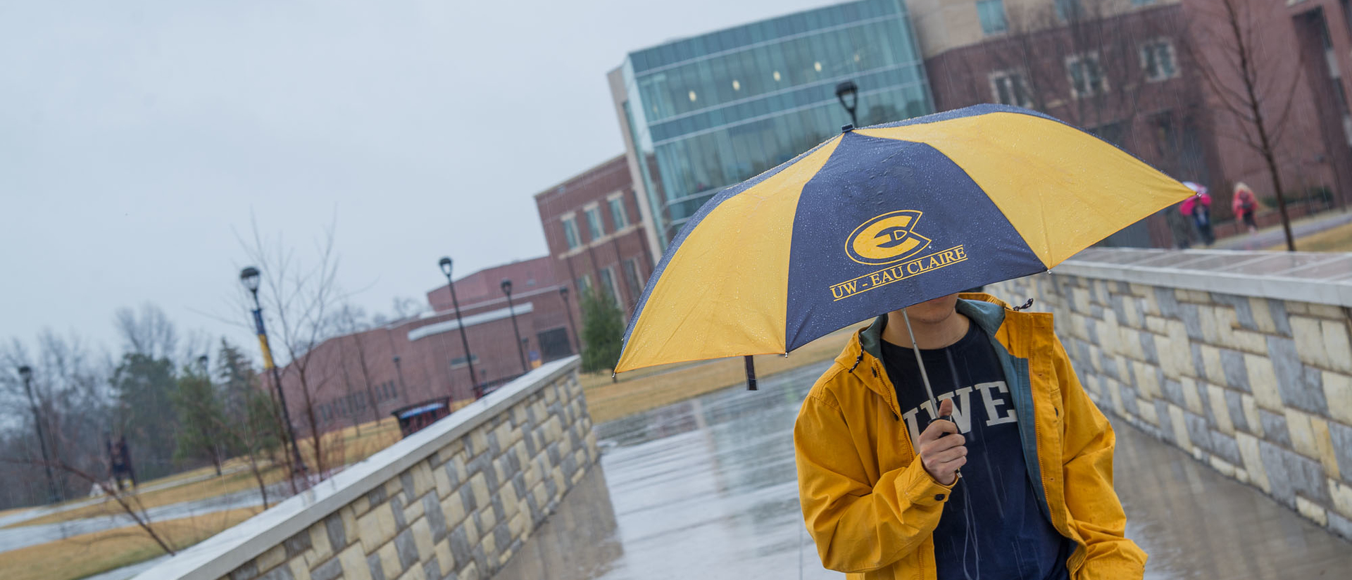 Student in the rain at UWEC