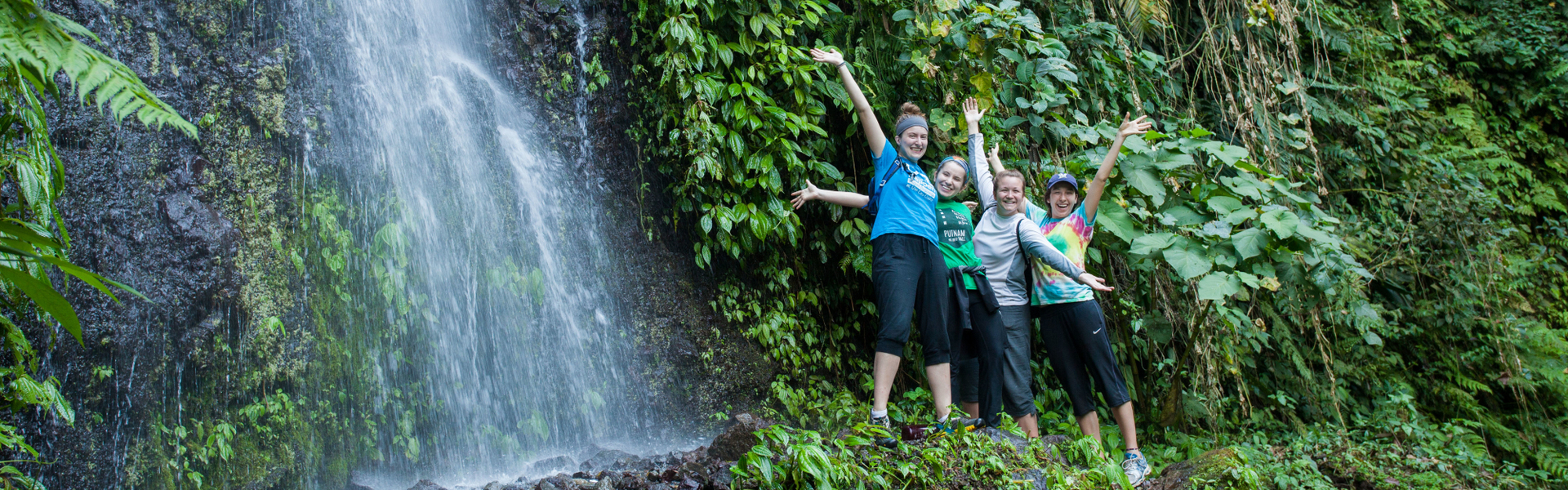 Students in jungle by a waterfall on immersion trip to Guatemala.