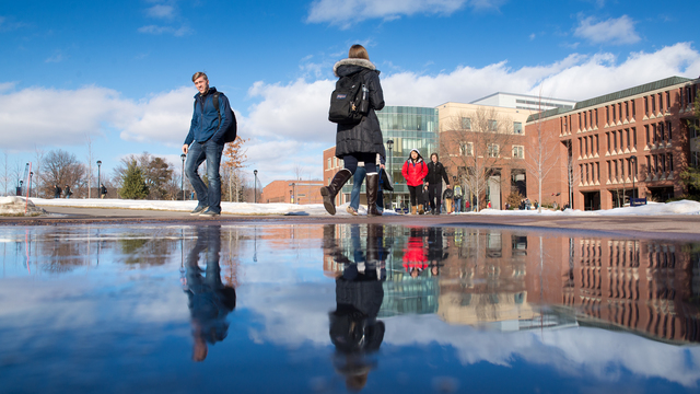 Students walking through campus on a sunny fall day.