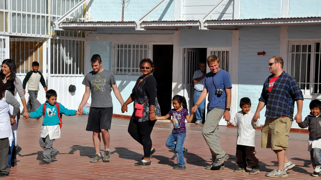 Students holding hands with children while studying abroad