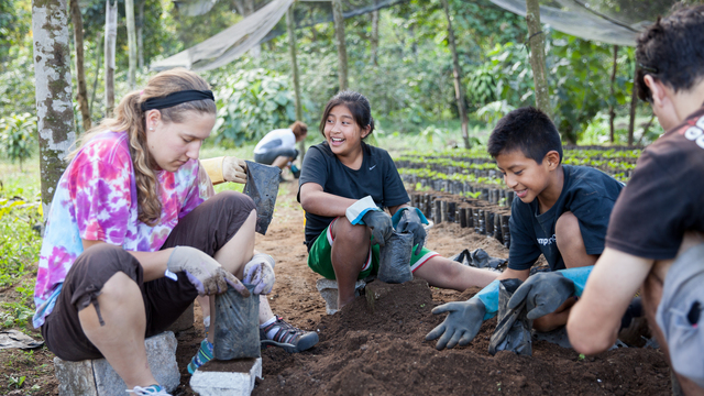 Student on immersion trip planting coffee in Guatemala