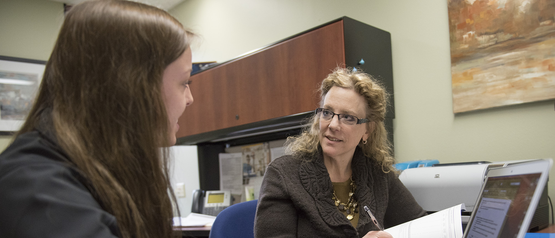 Faculty member talking with student.