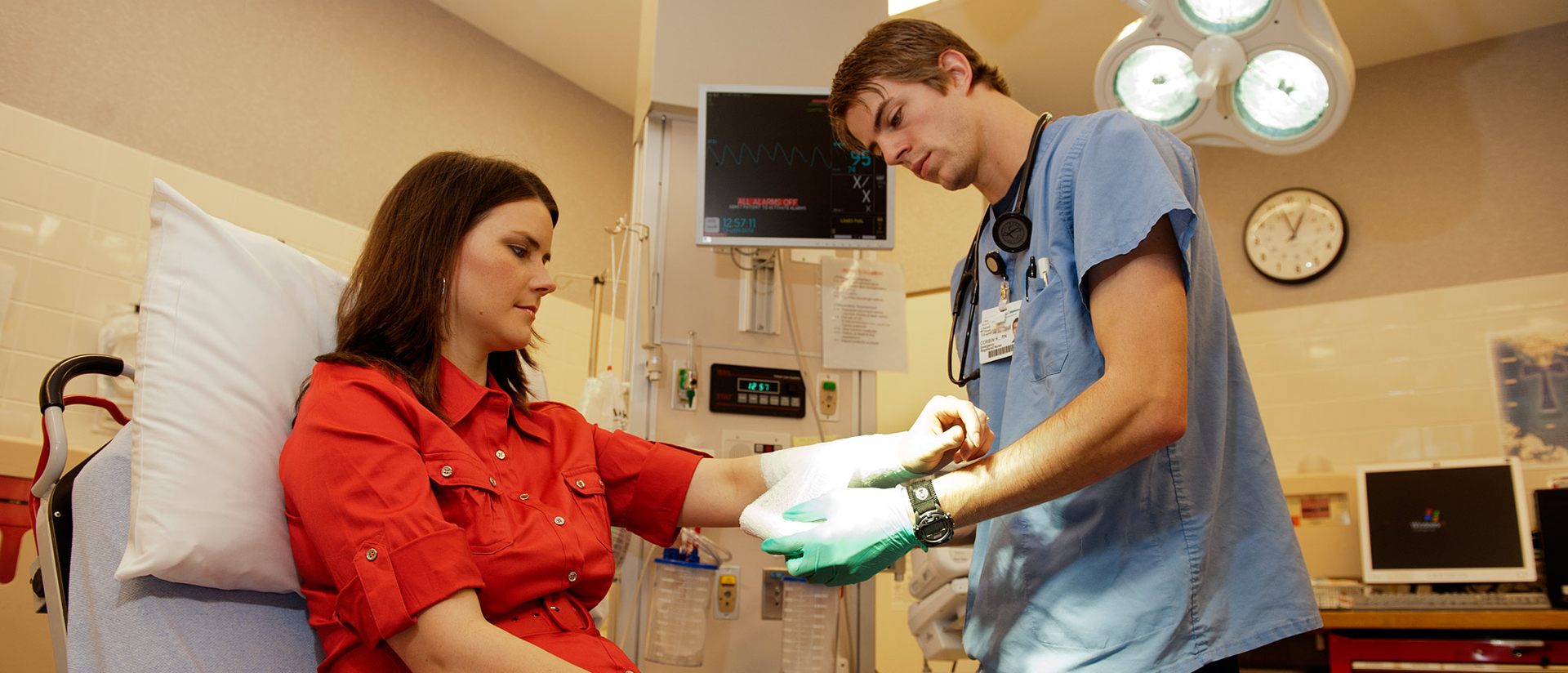 Nursing student taping up patient's forearm.