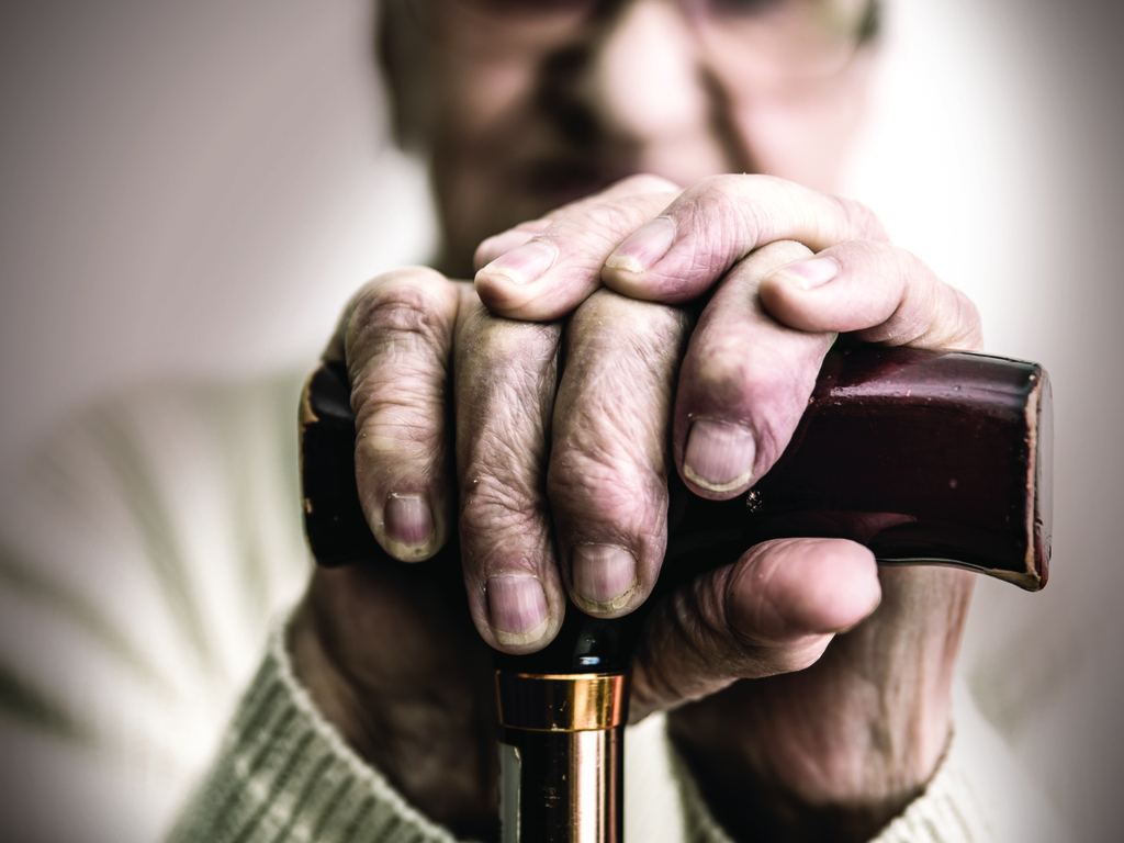 Older man with both hands placed on top of a cane held out in front of him.
