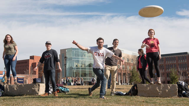 Students playing Frisbee in snow-free February campus mall
