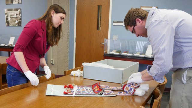 Shelby Miller examining Indian artifact in McIntyre archives.