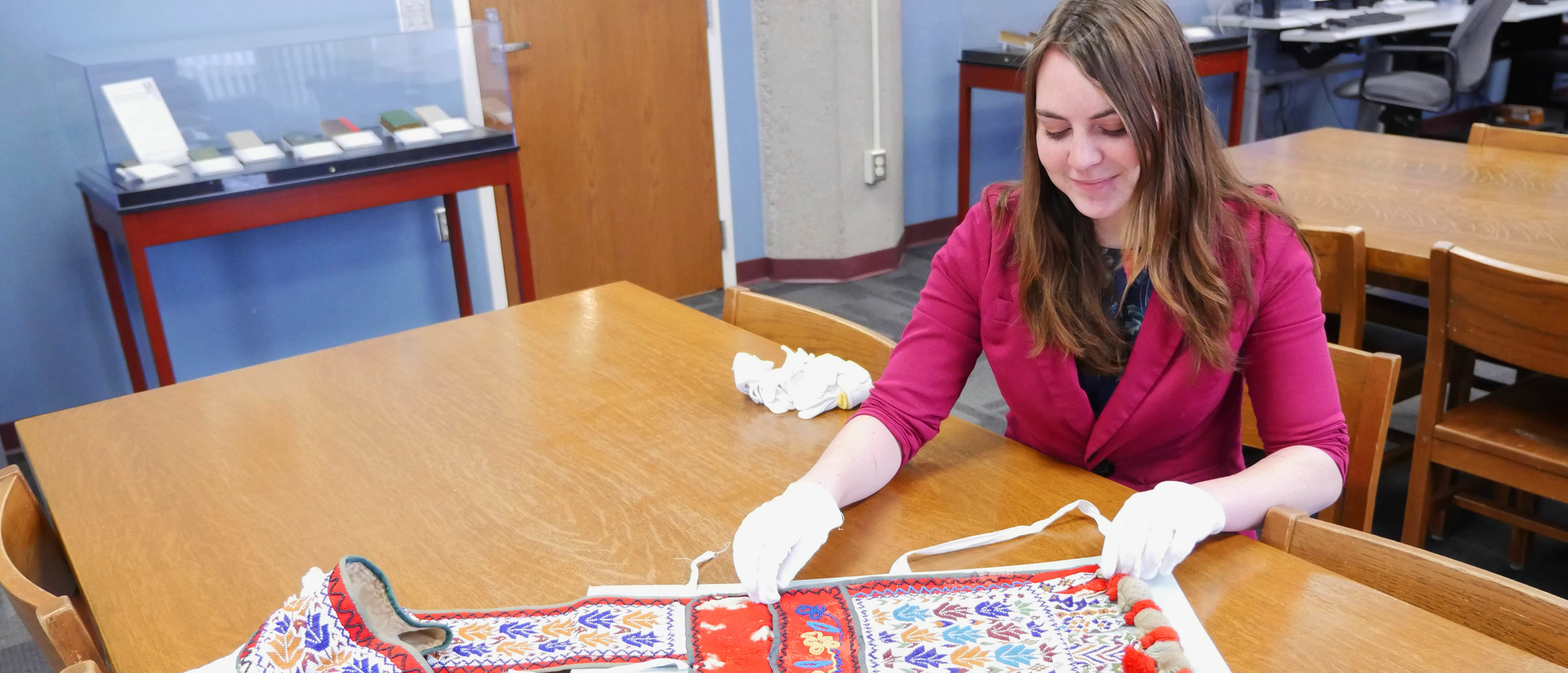 Shelby Miller in special collections working with Indian artifacts.