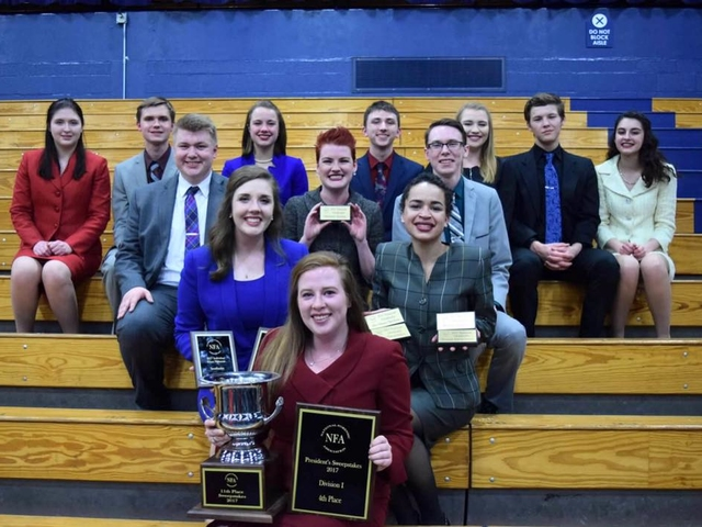 Forensics team at the 2017 NFA awards on the bleachers with their trophies.