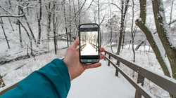 Student holds photo to take a picture in the winter.