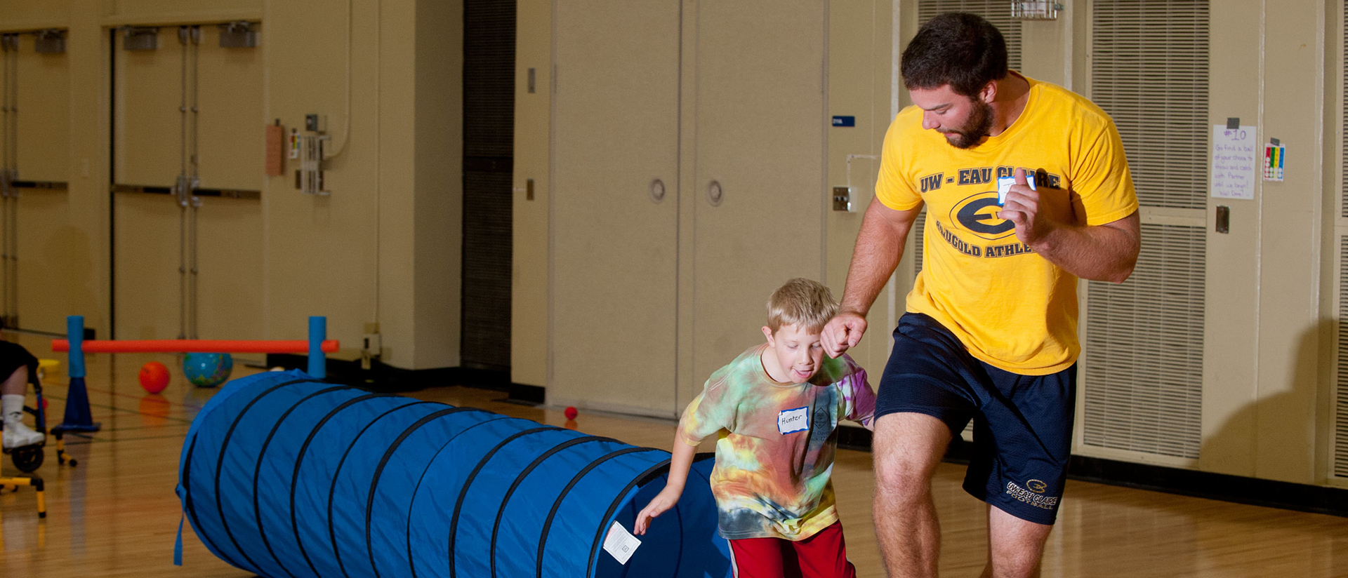 Student teacher helping boy get active.