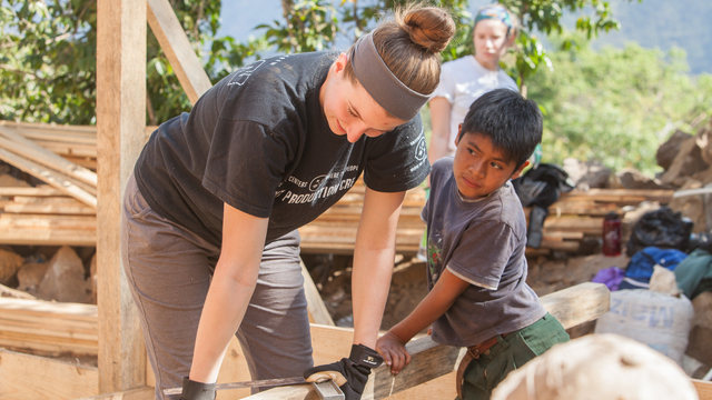 Student helping Guatemalan boy.