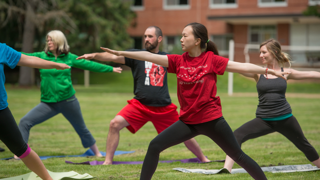 Students and faculty participating in a yoga class