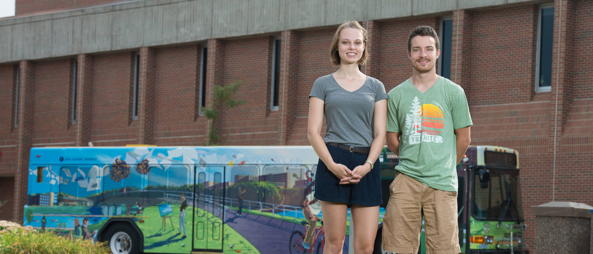 Roz Cashman and Lukas Carlson in front of Centennial Bus wrap.