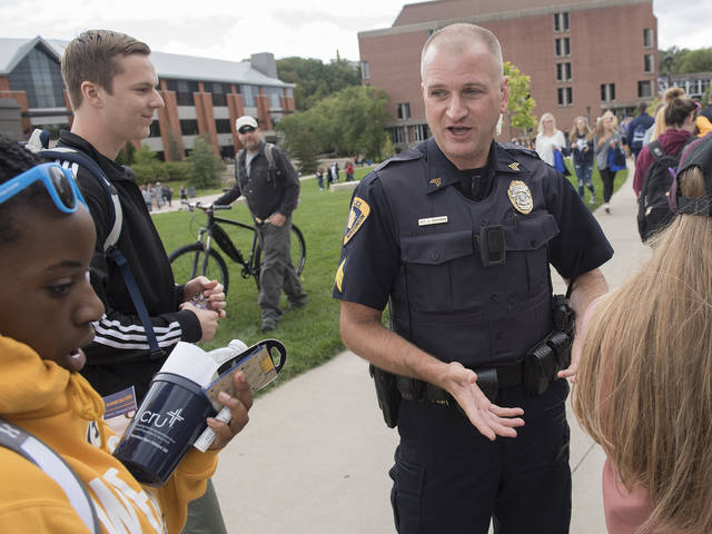 Campus police officer talking to new students on day one.