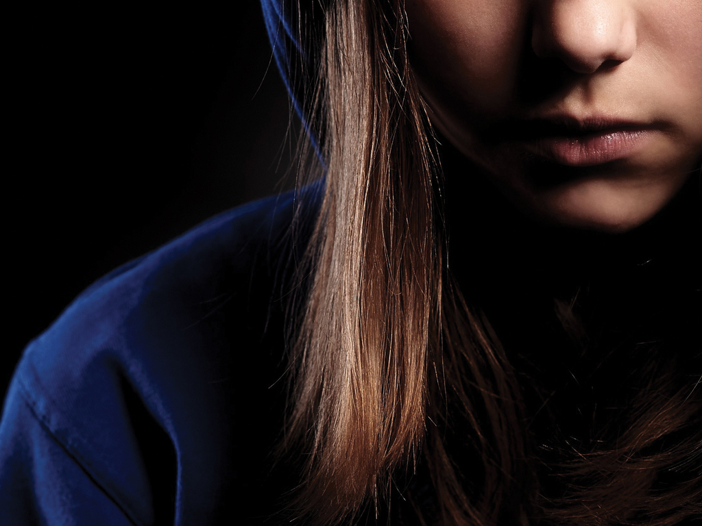 Partial head shot of a young girl wearing a blue hoodie