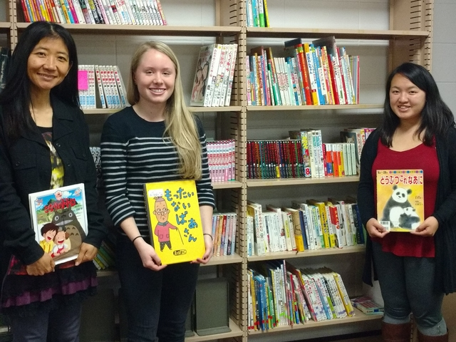 Students, Biranna Kosmer and Pa Dra Lee, and Dr. Tomomi Kakegawa with the new reading collection.