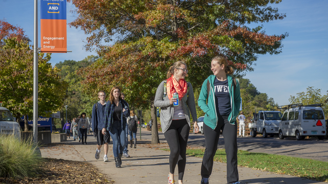Students walking on campus on fall day.