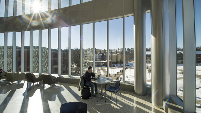 Student studying in sunny windows of Centennial Hall during winter