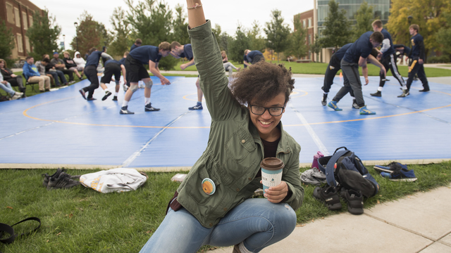 Female student holding coffee cup poses in front of outdoor wrestling practice