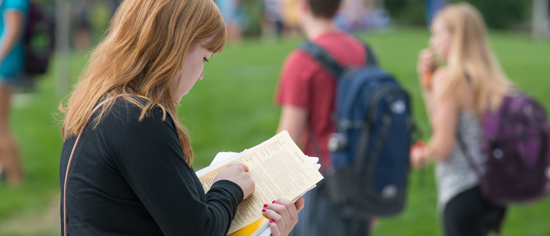 Student walking and reading papers